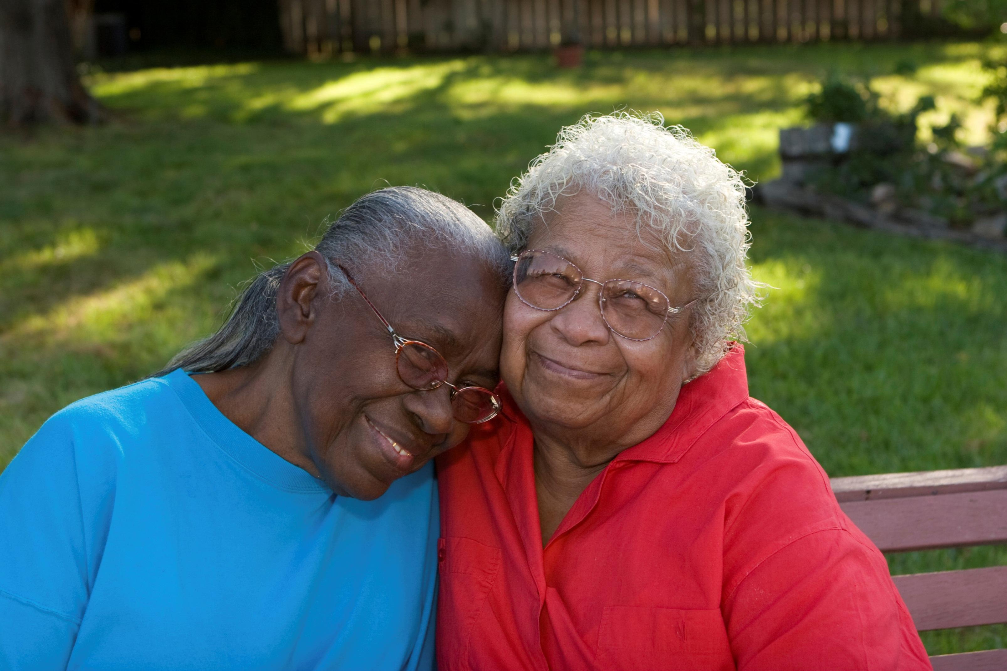 Adult daughter hugs her senior mother.