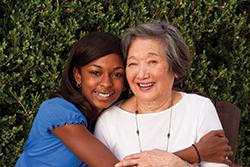 Volunteer hugs senior woman