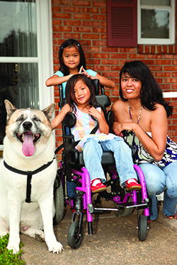Young girl with cerebral palsy poses with her family