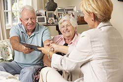 Retired Senior Couple Sitting On Sofa Talking To Financial Advisor Having To Sign Document