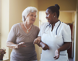 Elderly woman walking and talking with her home health nurse.