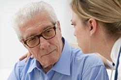Doctor consoling elder man