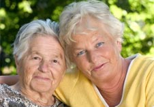 An adult woman poses with her elderly mother.