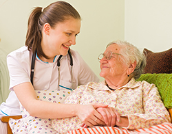 Young nurse helps elderly patient in her home.